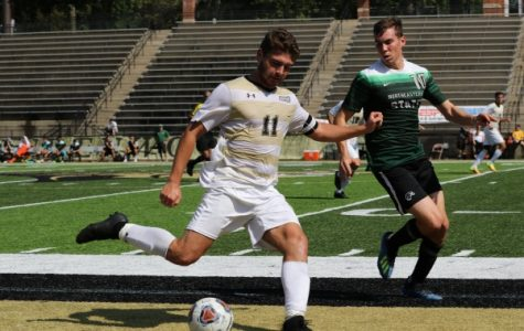Senior Thomas Hutcheson kicks the ball while pursued by Northeastern State University midfielder Trevor Reed on Sept. 28.  <br /> Photo by Maria Escalona.