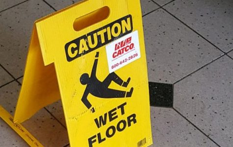 A wet floor sign in the lobby of Guffey Hall the day after the water damage.  <br /> Photo by Matt Hampton.