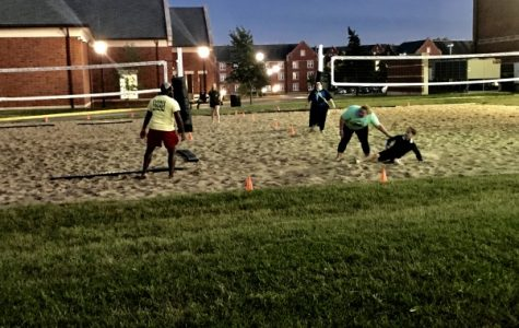 Cabbie Anthony Madison, left, stays planted in the sand while Molly Tiemeyer, right, sweeps in on her younger brother who also participated. <br> Photo by Lauren Pennock