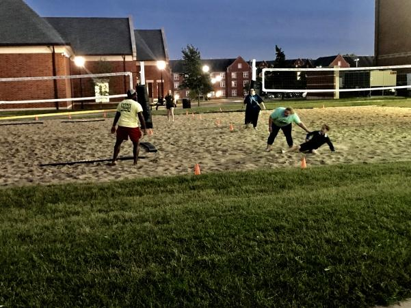 Cabbie Anthony Madison, left, stays planted in the sand while Molly Tiemeyer, right, sweeps in on her younger brother who also participated.  Photo by Lauren Pennock