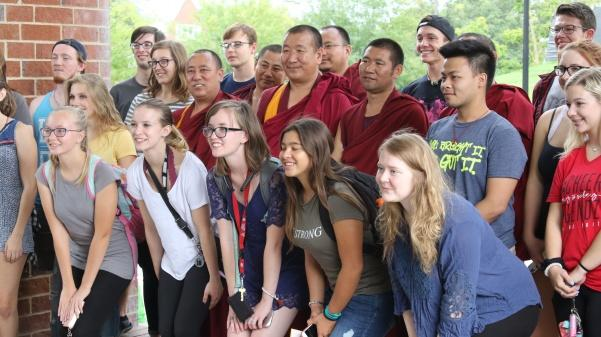 Students+gather+around+the+Tibetan+monks%2C+in+red%2C+after+the+monks+finished+prayer+chanting+under+the+Spellmann+Center+clock+tower.%0A+Photo+by+Kayla+Drake