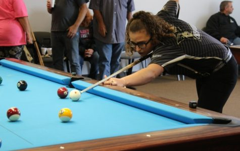 April Larson, a freshman majoring in finance, prepares to execute a shot  in the Lindenwood Billiards Arena. Larson is a professional player and billiards national champion. <br /> Photo by Merlina San Nicolás