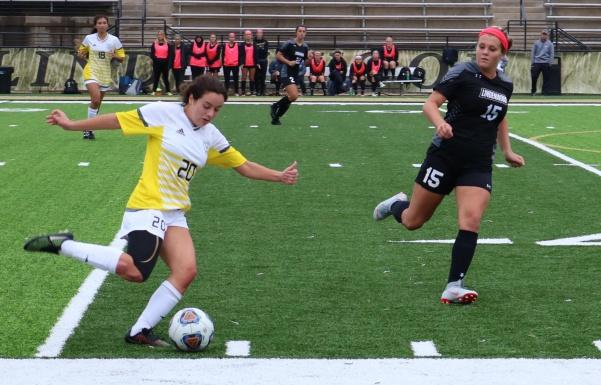 Forward Morgan Weller runs to stop a kick by Fort Hays State freshman Jenna Prince.  Photo by Caleb Riordan.