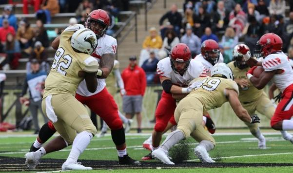 Lions defensive end Arsante Conners (92) and linebacker Nate Blanchard (49) get shut down by the UCM defense, paving a way through the line for  their quarterback Devante Turner (3).  Photo by Kayla Drake
