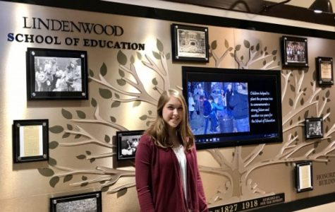Ashley Holdmeier stands in front of the School of Education's brand new Centennial Wall, displayed in Roemer Hall. <br /> Photo by Lauren Pennock.