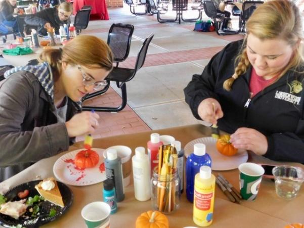 Molly Tiemeyer paints mini pumpkins with Lindenwood graduate student, Bailey Kinney, left, at the Commuter Life: Pumpkins & Public Safety event.  Photo by Lauren Pennock.