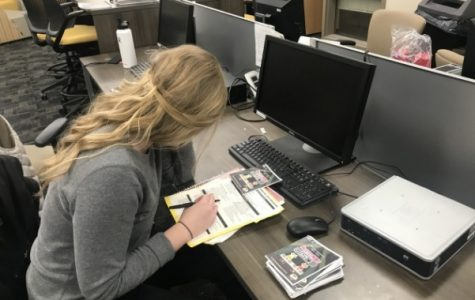 Haley Cluck stationed in the Student Involvement office, going over final details for Thursday's Headphone Disco party. <br> Photo by Lauren Pennock.