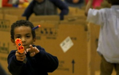 A Boys and Girls Club member shoots a nerf bullet at one of his friends during the nerf war on Nov. 30. <br> Photo by Kayla Drake
