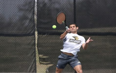 Freshman Juan Albin hits a volley during the doubles match against Missouri Valley on Saturday afternoon.  Photo by Merlina San Nicolás.