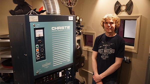 Tom Ostertag, class of 2013, poses next to his movie theater projector on the top floor of his converted school building in St. Charles.  Photo by Mitchell Kraus