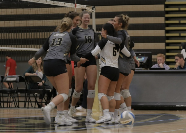 In the center, Kelly Willson (16) celebrates with her teammates after winning a point against Flagler College on Friday night at Hyland Arena.