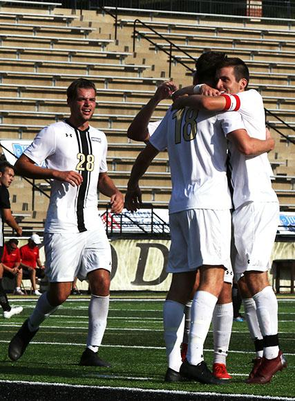 Midfielders Cooper Wilson (28) and Leon Silva celebrate with Luke McBeth (18) after he scored his second goal of the game off a penalty shot.