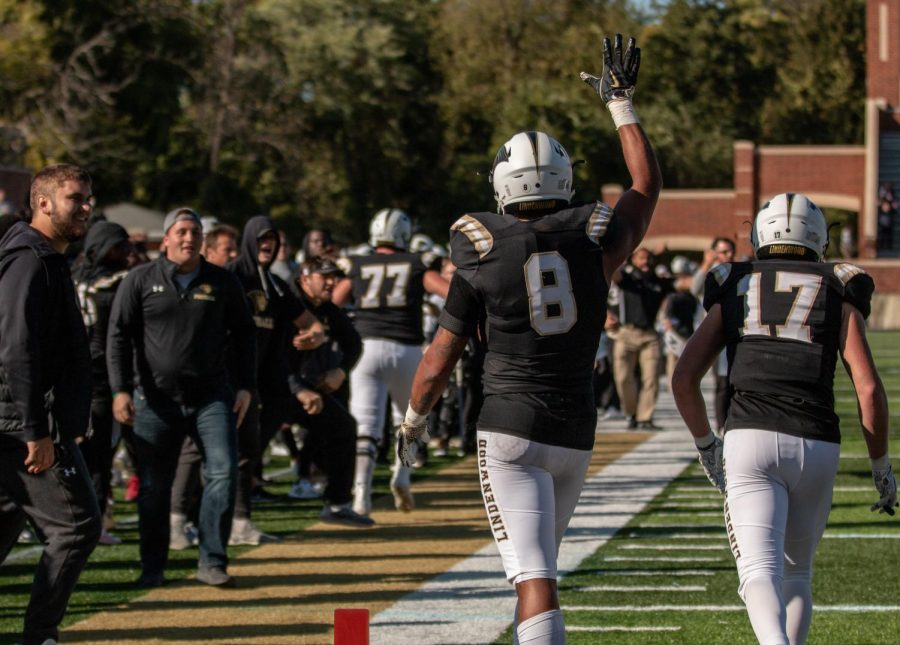 No. 8 Erik Henneman waves at his teammates during the homecoming match against Truman State. Henneman locked in the winning touchdown to give the Lions an exciting win Saturday at Harlen C. Hunter Stadium.