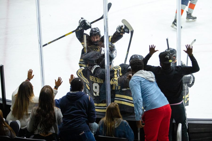 The Lindenwood men's ice hockey team celebrates after leading 3-0 in the second period, while Lindenwood women's ice hockey cheers along  the boards.