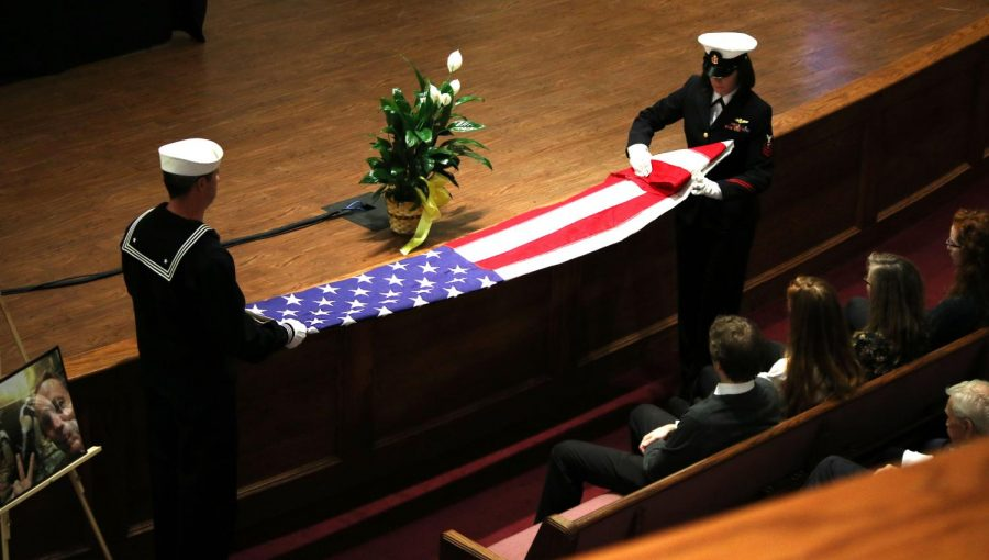 From the right: Petty Officer 1st Class Lee Newbold and Petty Officer of the Navy Tarah Snow fold the American flag to give to Anderson's wife, Karen.