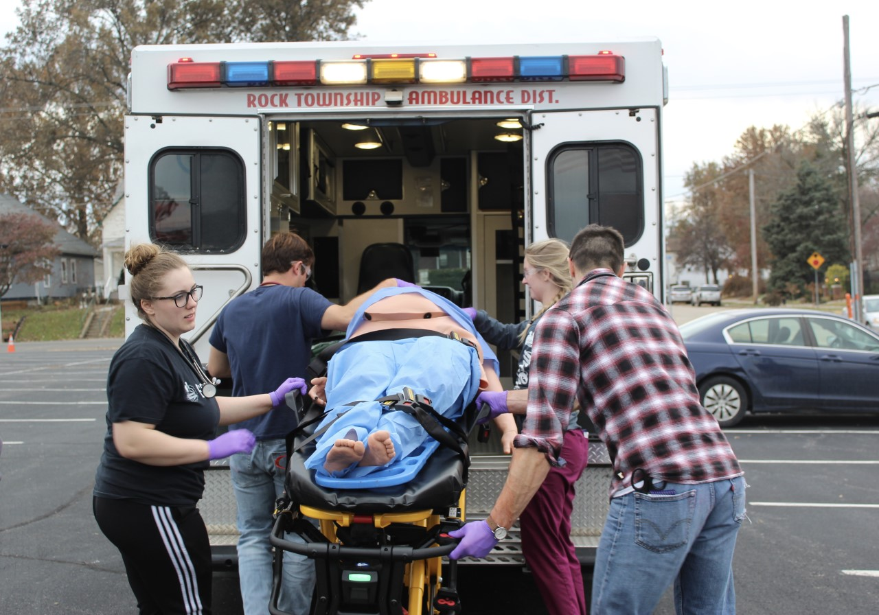 Lindenwood paramedic students lift a fake car accident victim into an ambulance in under 10 minutes during their Trauma Lanes simulation.