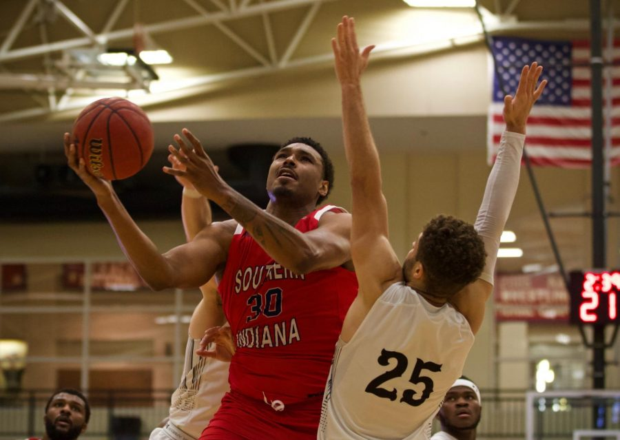 Southern Indiana forward Josh Price (No. 30) scores on Lions guard Cameron Scales in the fourth quarter. This game marks a 9-game losing streak for the Lions.