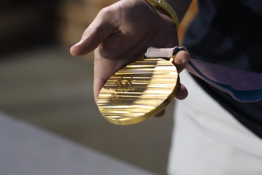 During a signing of his book, Josh Pauls shows his sled hockey gold medal from the 2018 Paralympics in PyeongChang, South Korea.