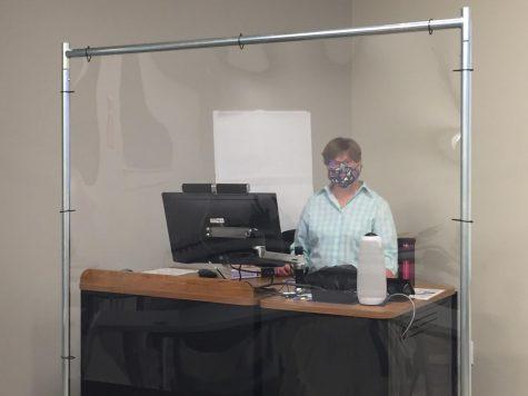 Ana Schnellmann, an English professor, teaches class behind a plexiglass barrier.