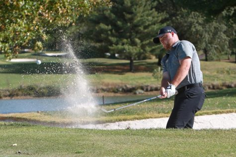 Junior Caleb Picker attempts to chip his ball out of the bunker during a tournament in the fall of 2020.