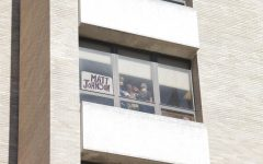Matt Johnson waves to cars as they drive past his window in support.