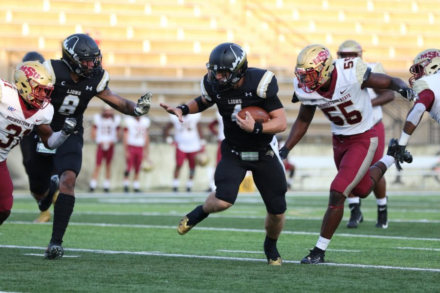 Quarterback Cade Brister (right, #4) runs past a defender and prepares for contact with another in Lindenwoods 28-27 loss against No. 16 Midwestern State University Texas on Sept. 14, 2019.