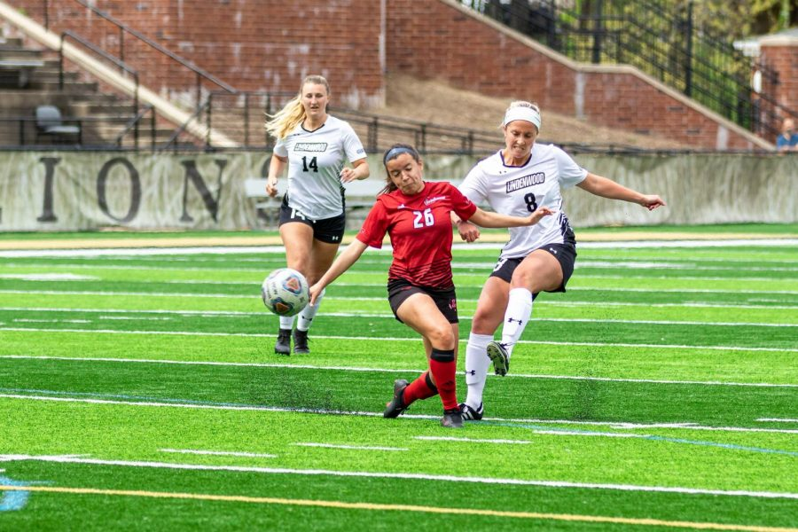 Grace Blair (#8, right) kicks it away from a Lewis defender on April 19.