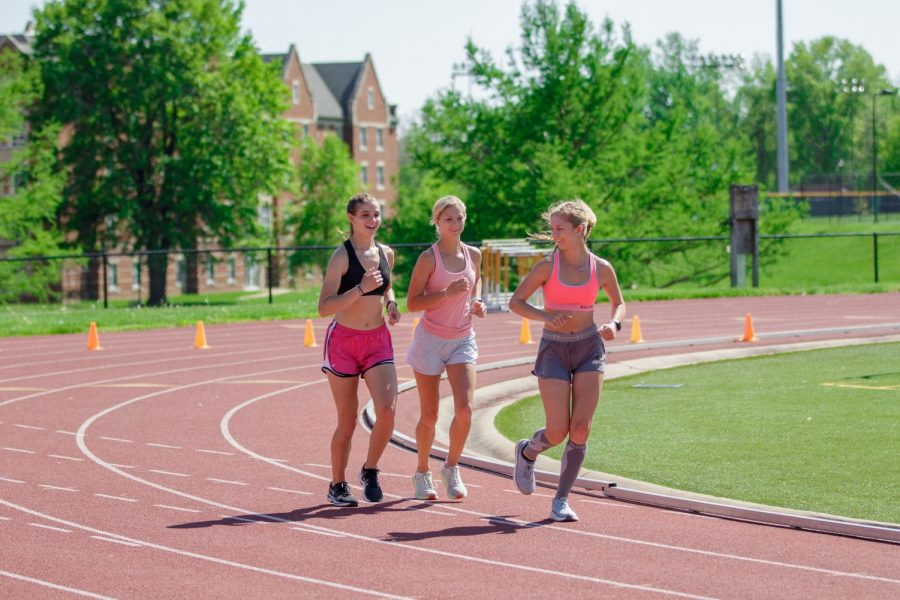 Athena Viers (left), Courtney Reid (middle), and Sydney Reid (right) jog around the Lindenwood track on April 30.