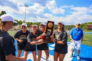 Several women's lacrosse players celebrate with the trophy after their national championship win (14-12) over Queens University on May 23 in Salem, Virginia. Photo provided by Ryan Hunt