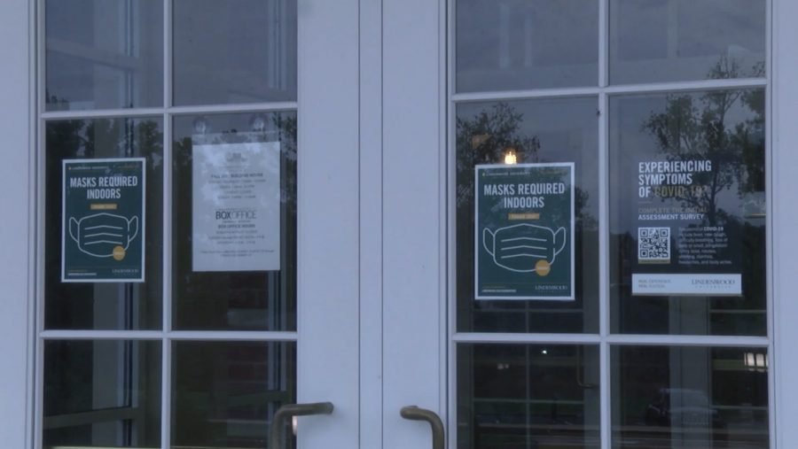 Signs posted on the doors of J. Scheidegger Center telling students, faculty, and other visitors to wear a mask inside the building.